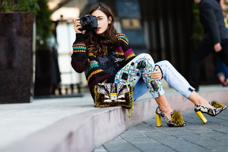 woman with brown hair sitting on street curb looking through a camera