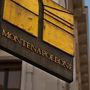 Street sign for via Montenapoleone in Milan with a blue sky behind the sign