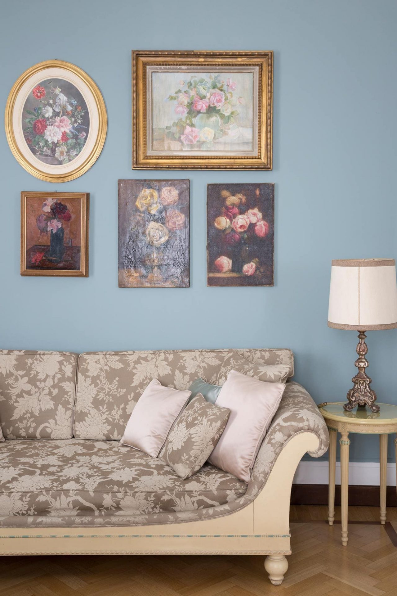 light blue wall with five framed art pieces, a lamp on a table and part of a couch with three pillows