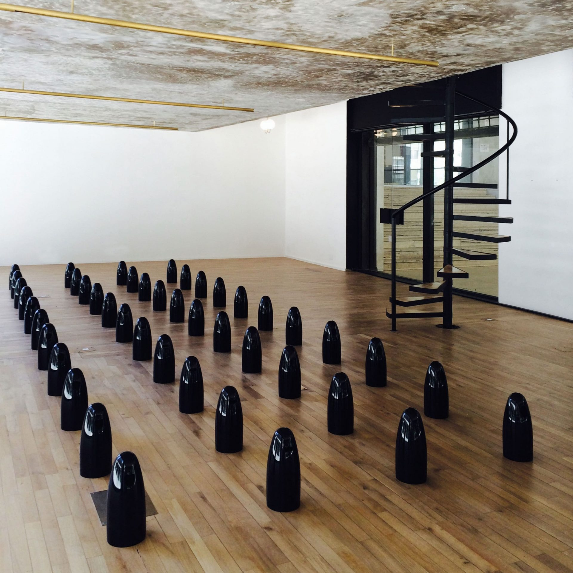 small black ceramic dolls are lined along the wooden floor of a small room with white walls and a spiral staircase
