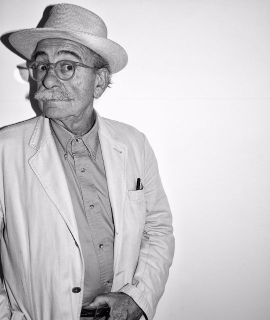 portrait in black and white of ugo la pietra an older man wearing glasses, a hat, and a mustache