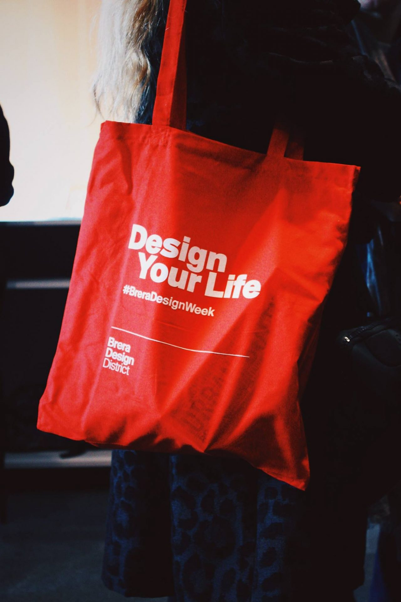 red tote bag with white text stating design your life