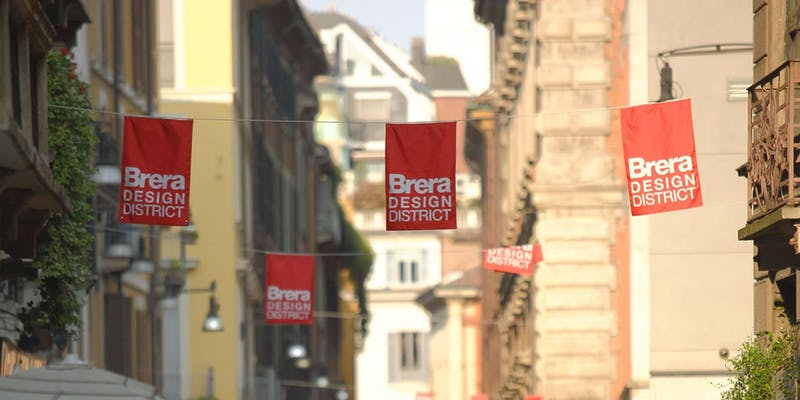 street scene in milan with red flags with white text of brera design district
