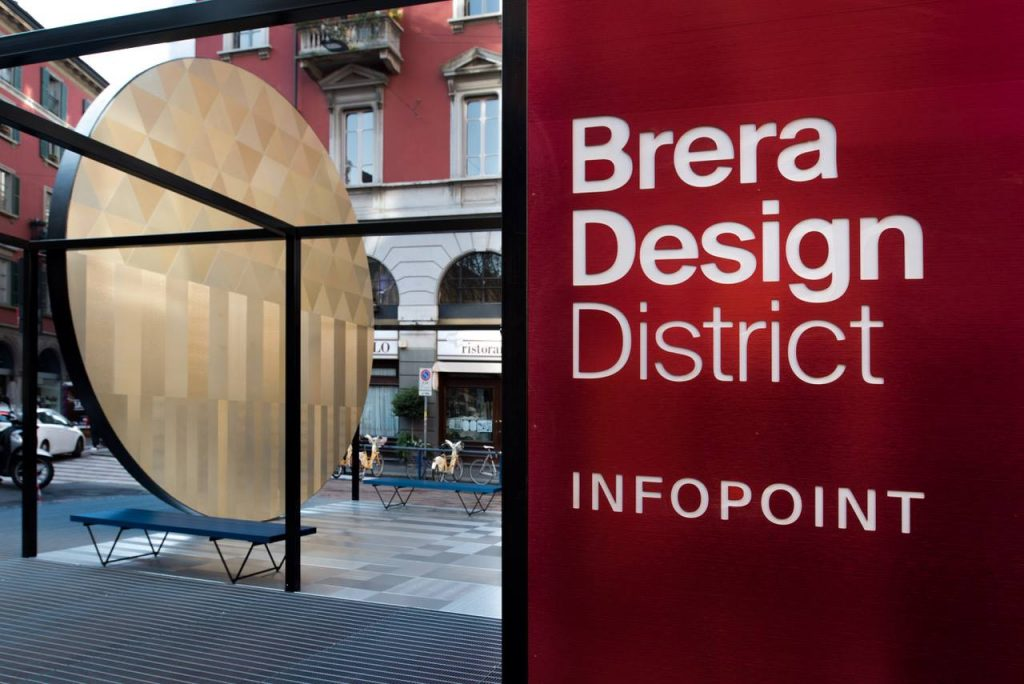 red sign with white text declaring brera design district in milan