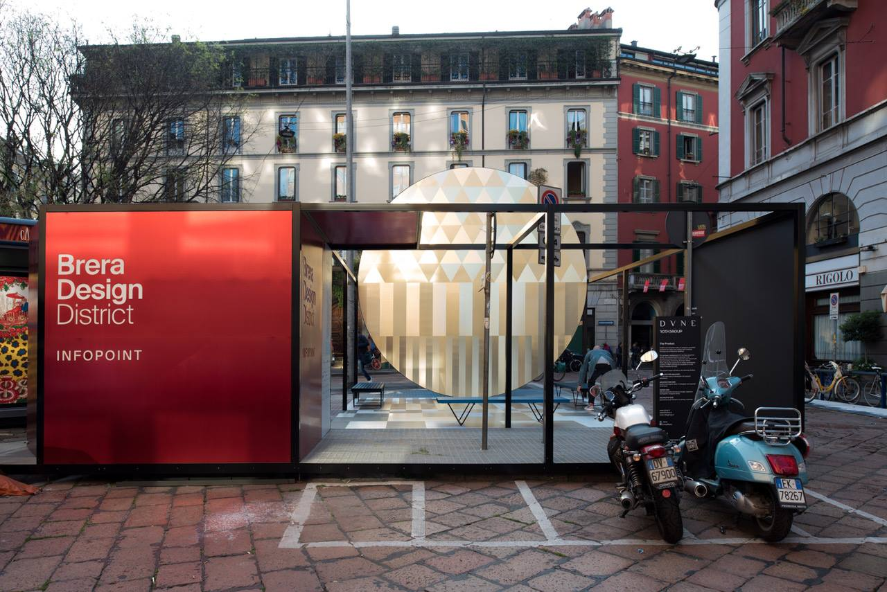 outdoor center in milan with historic buildings surrounding an info point