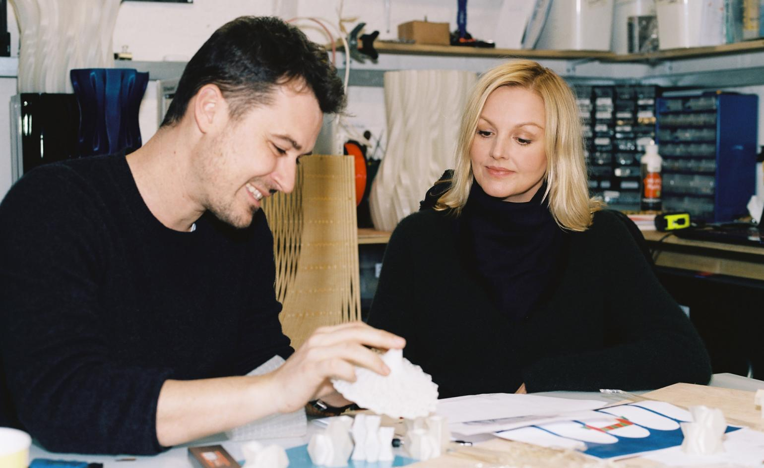 a man in a black shirt with black hair sitting at a table with a woman with blonde hair in a black shirt working in a studio