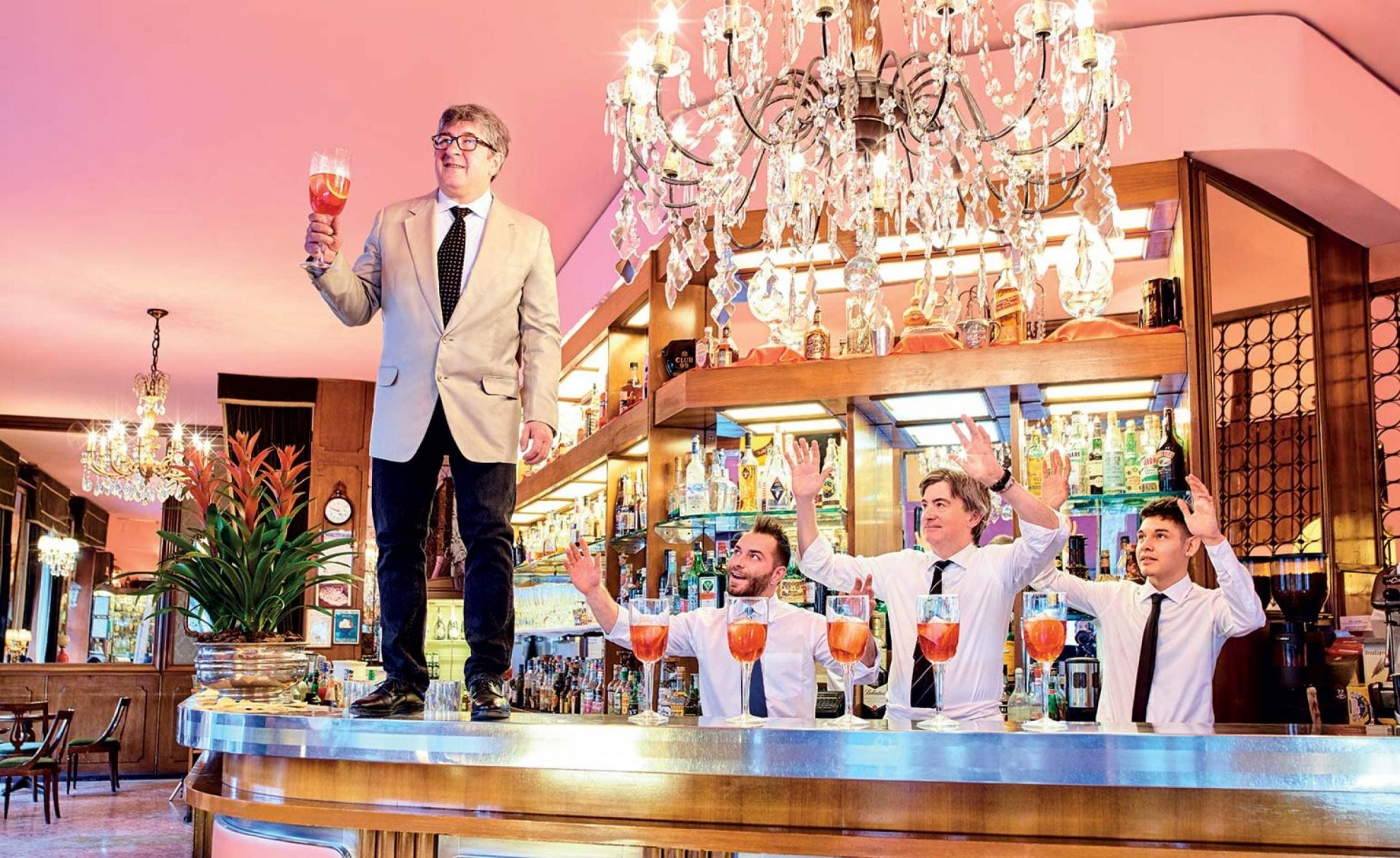 a man in a suit standing on top of a bar holding a drink with three men in suits behind the bar holding drinks
