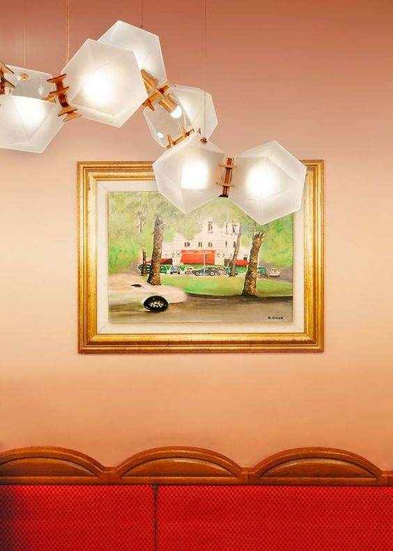 red sofa with framed art on wall and geometric lighting feature on pink wall