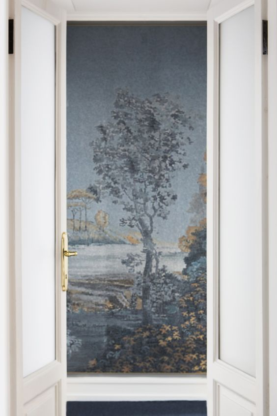 white doorway opening to a mosaic wall made of tiny glass squares of a tree and water scene