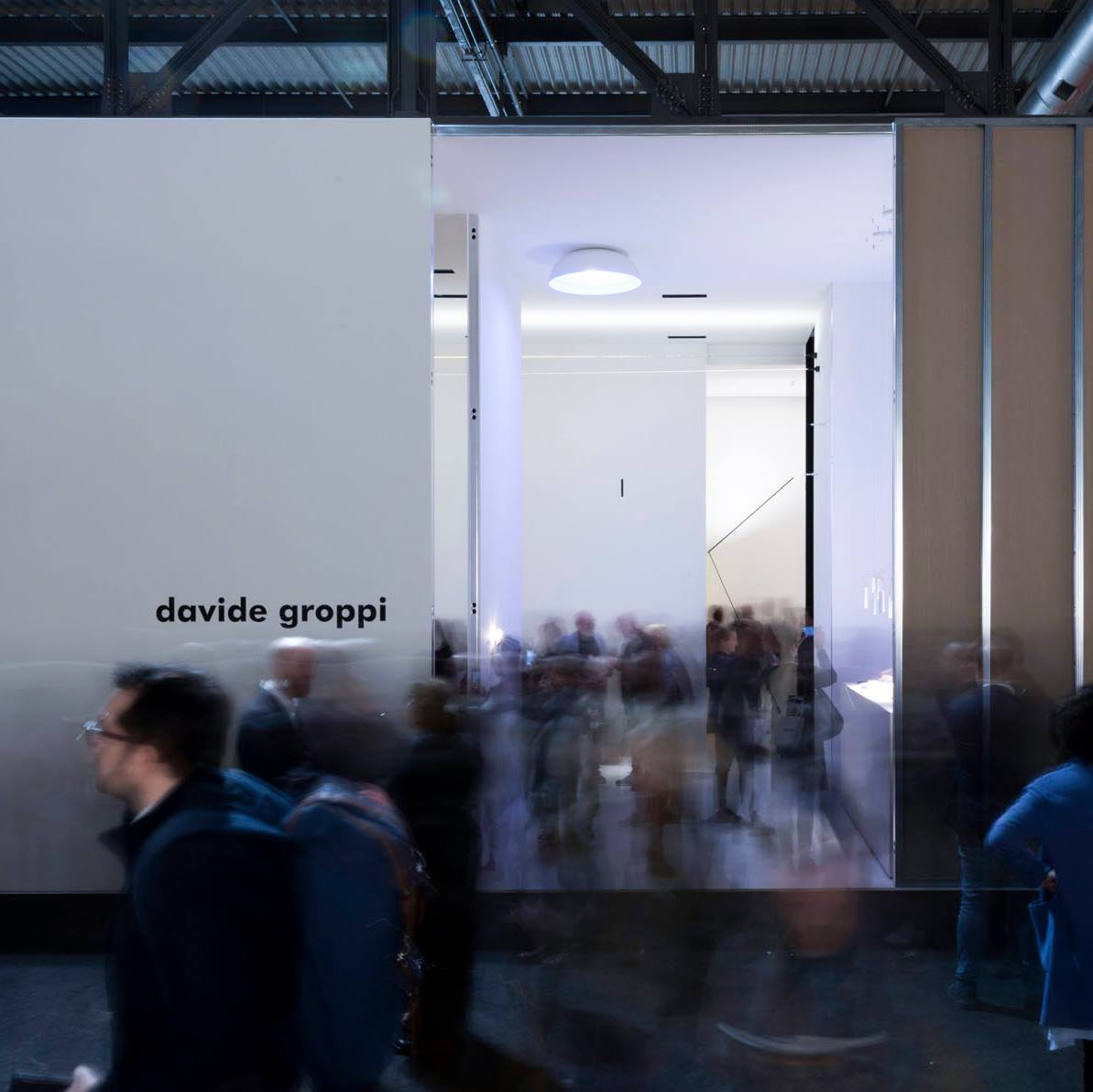 white structure with black text 'davide groppi' at euroluce 2019 with people moving and walking through the space