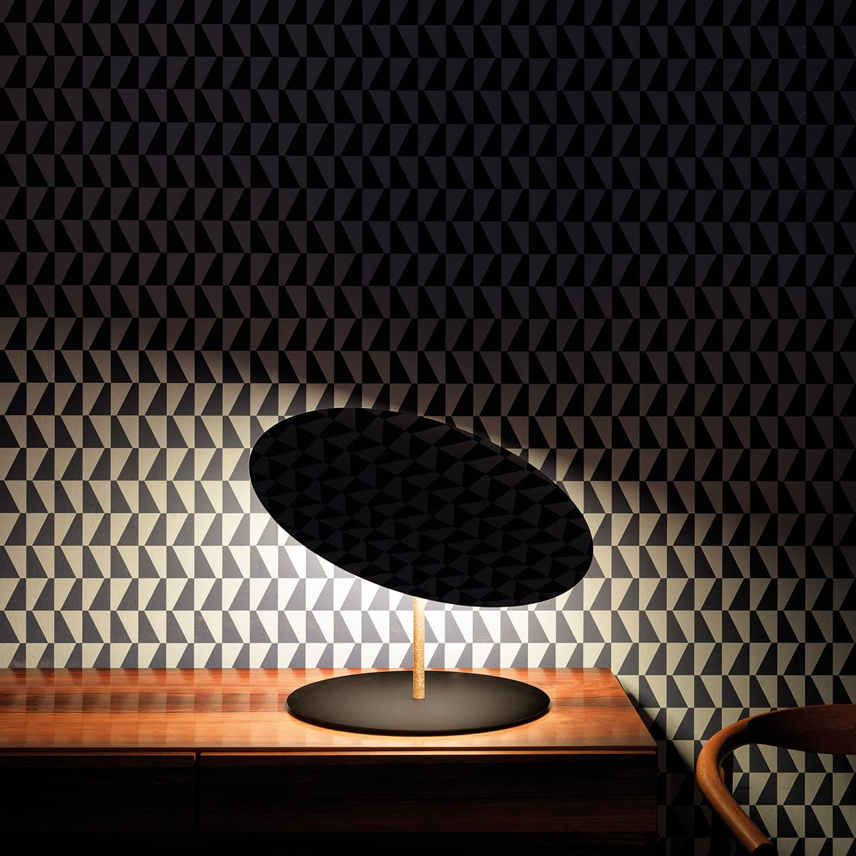 small round table lamp on a wooden desk with a patterned wallpaper with black and white geometric shapes