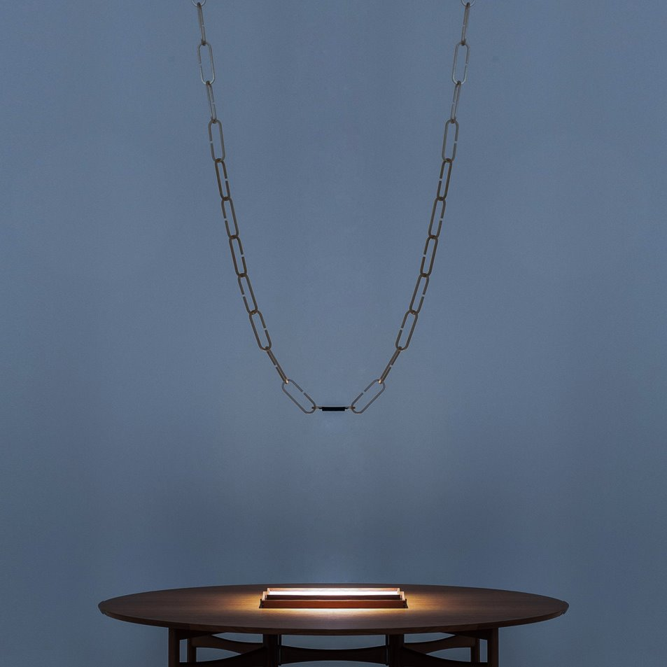 a large chain with a light at the end of the chain dangles above a small table with a grey wall background