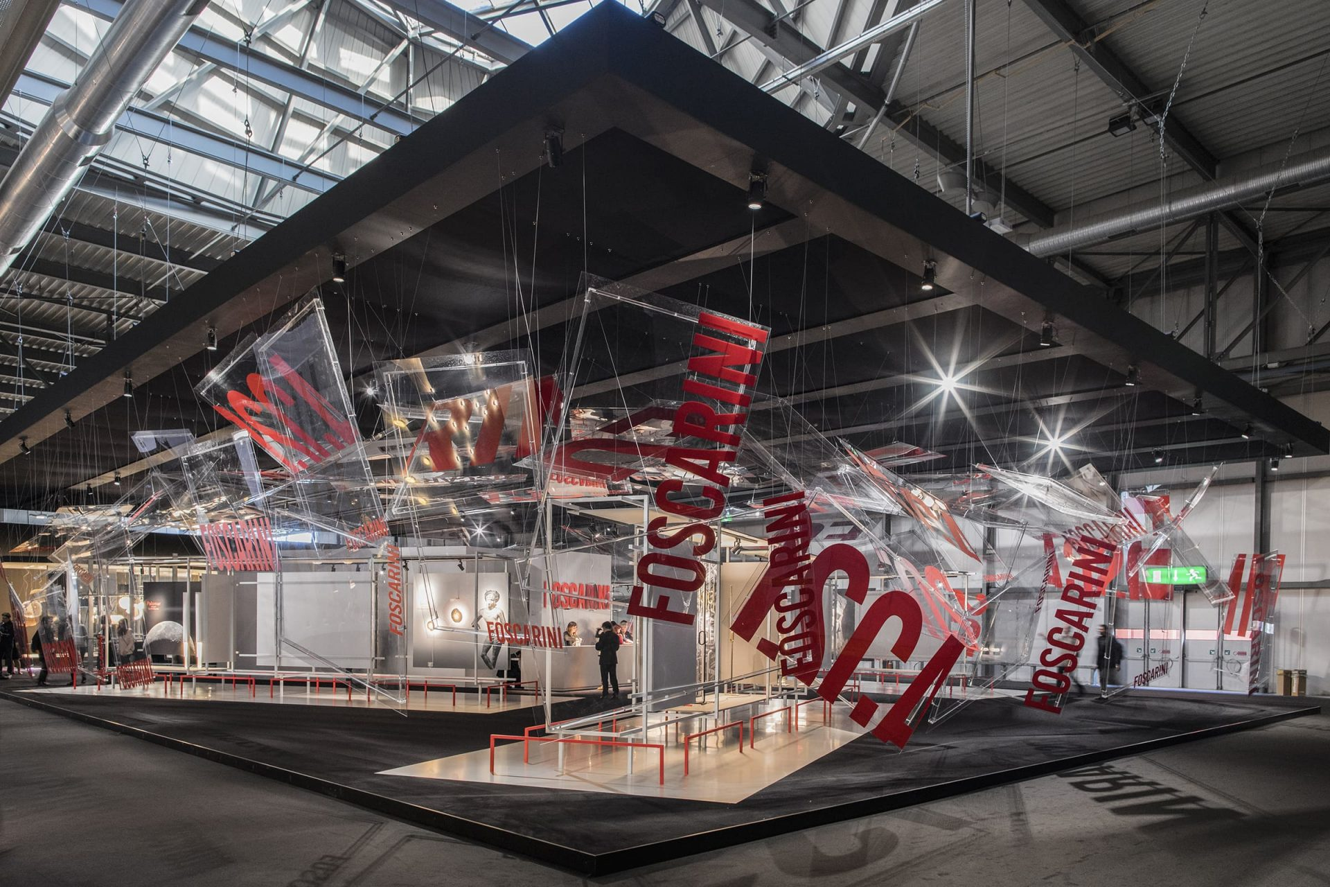 booth at Euroluce with Foscarini in red text printed on various squares suspended from the ceiling, displaying light systems and lamps