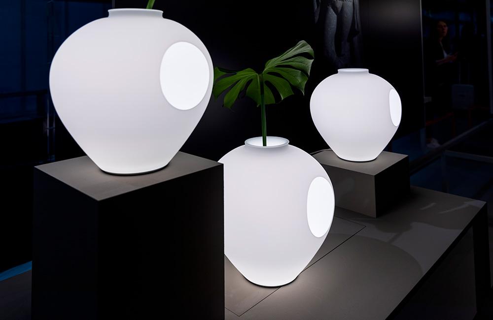 three large white lamps with round circles displayed on black platforms at Euroluce