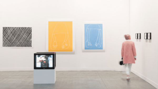 yellow and blue framed artworks on the wall with a woman in a pink coat walking by
