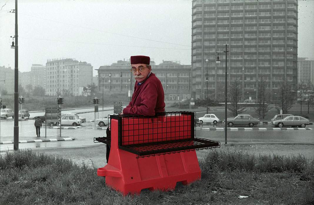 old man with black hat sits on a red bench overlooking a black and white cityscape