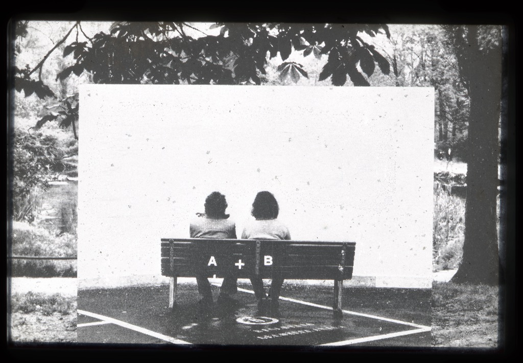 photograph of two people sitting on a bench
