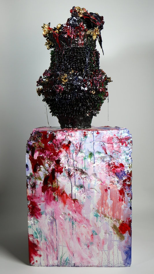 black vase covered in red, purple, blue, and yellow paint and resin