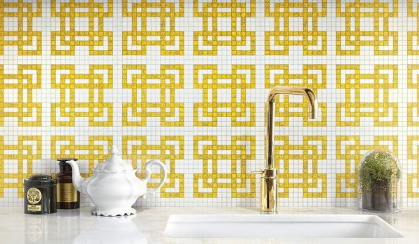 Italian Decorative wall tiles in the backsplash of a kitchen with a shining golden tap