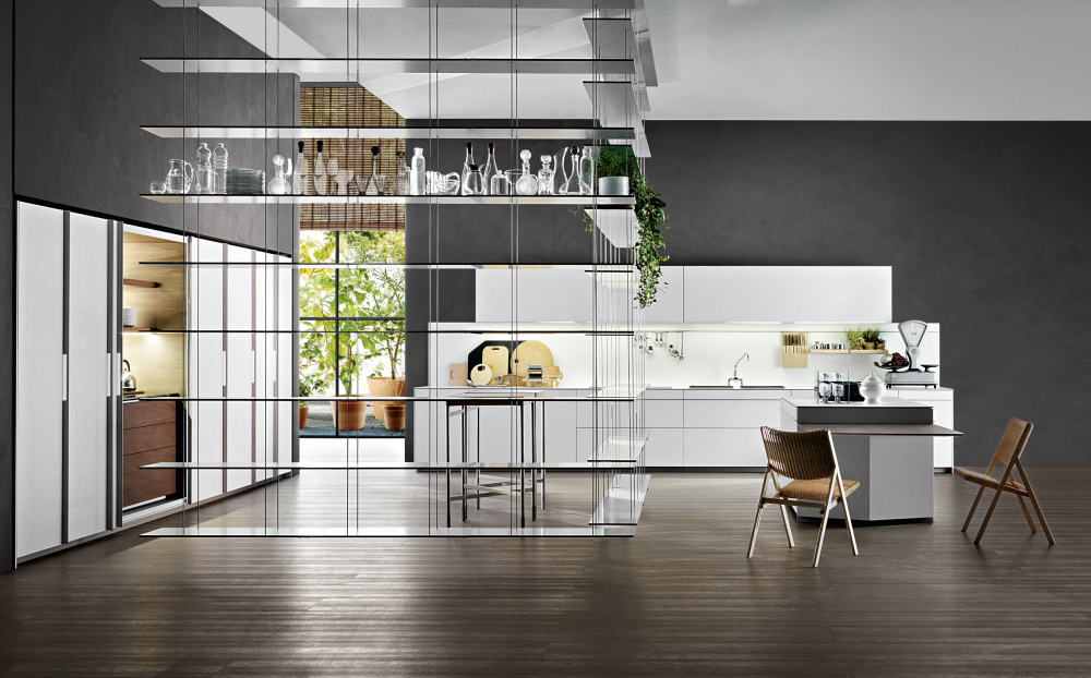 Vela kitchen by Dada kitchen a modern Italian kithchen brand presentented in a contemporary setting with Graduate library system hanging from the ceiling