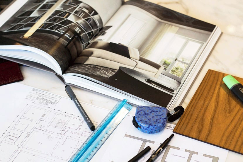 an Italian furniture catalogue next to a 2d floorplan of an Italian interior design project with a measuring tape used by our Italian interior designers online