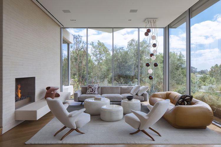 modern living room with large glass windows designed by a high end interior designer in los angeles